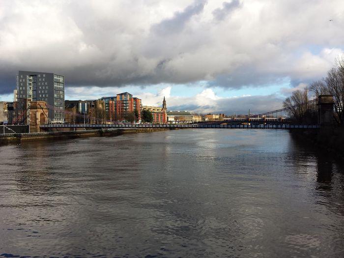 Suspension bridge over river clyde in city against sky