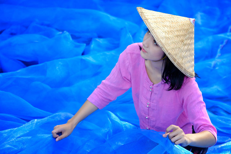 Young Woman Wearing Asian Style Conical Hat Holding Blue Tulle Netting