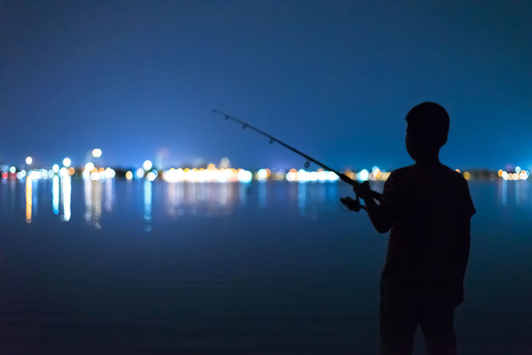 Rear View Of Silhouette Boy Fishing In Sea At Night
