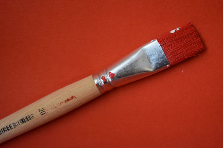 Close-up of paintbrushes against red background