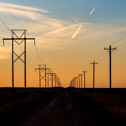 Electricity pylon by road against sky during sunset