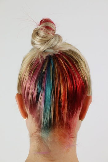 Rear view of woman with dyed hair against white background