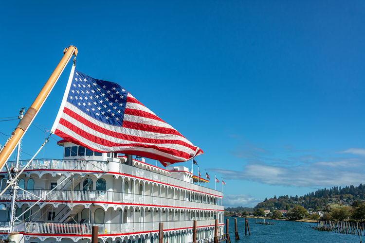 American flag waving in the wind with an old time riverboat in beautiful Astoria, Oregon Astoria Oregon Pacific Northwest  Columbia River River Travel Travel Destinations Tourism American Flag American Flag Riverboat Columbia Sky Blue Water Nature Striped Waterfront No People Clear Sky Independence Outdoors Day