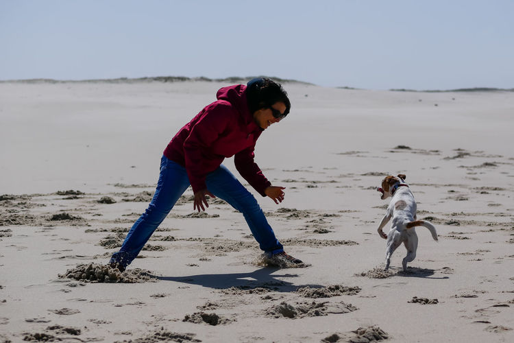Rear view of girl playing with dog on beach