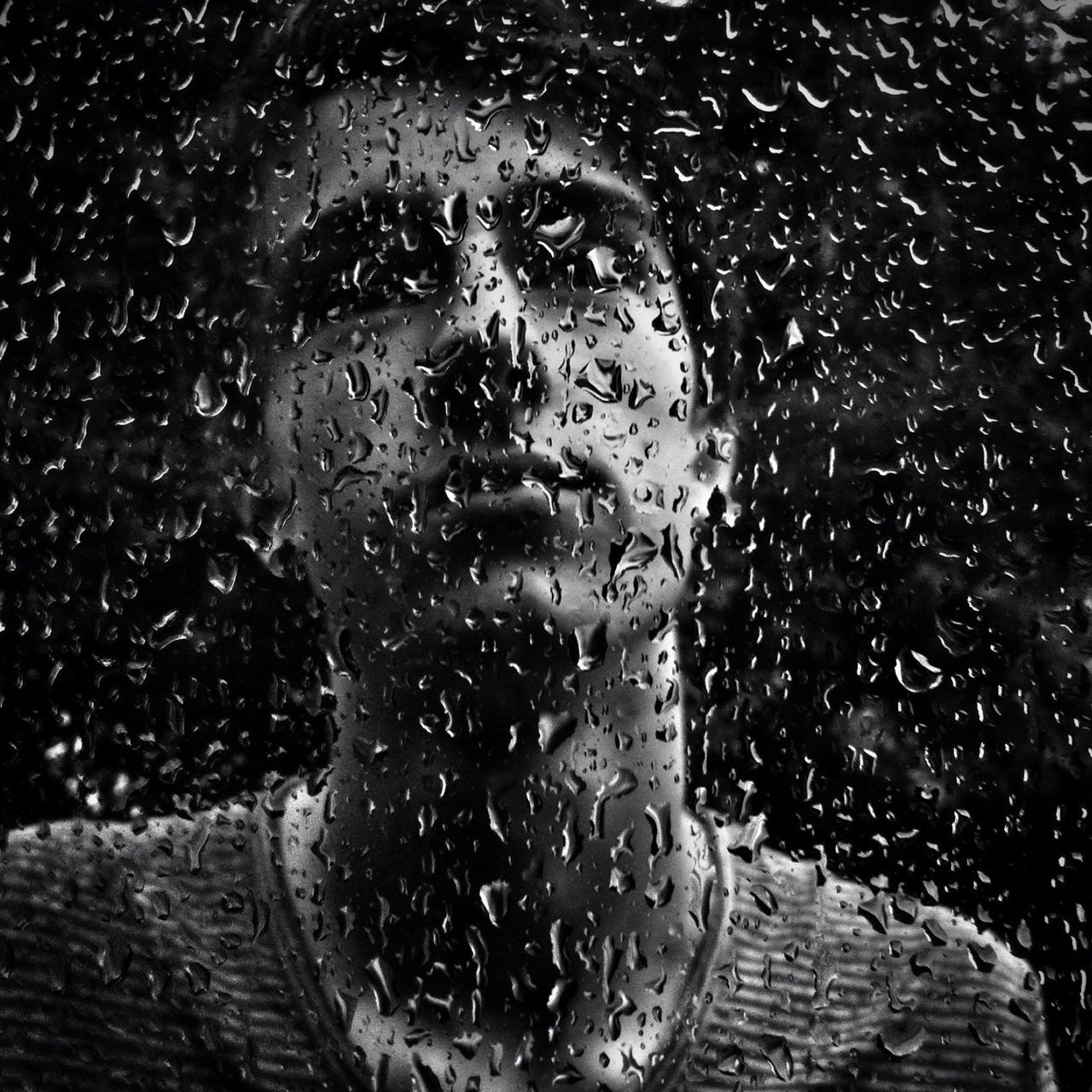 Close-up of man behind glass with waterdrops