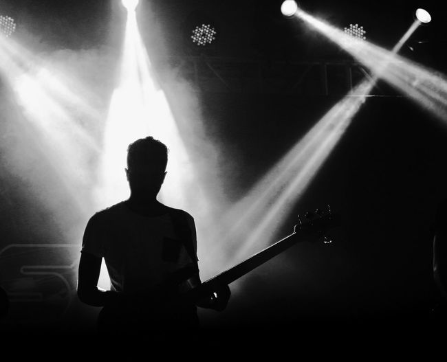 Silhouette man  standing playing guitar in illuminated music concert
