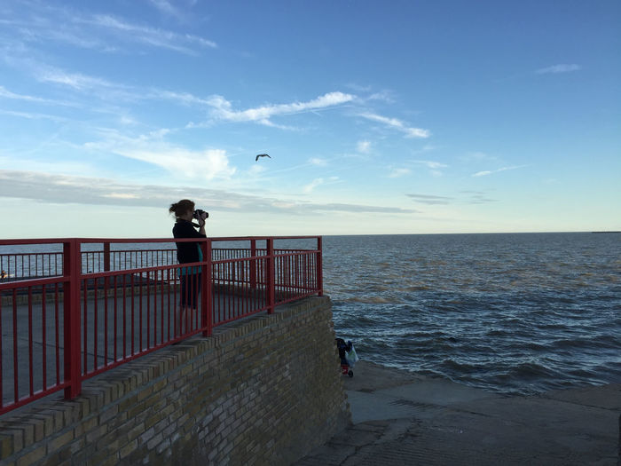 Side view of woman photographing on pier by sea against sky