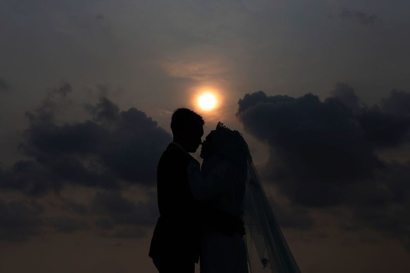 Silhouette wedding couple against sky during sunset