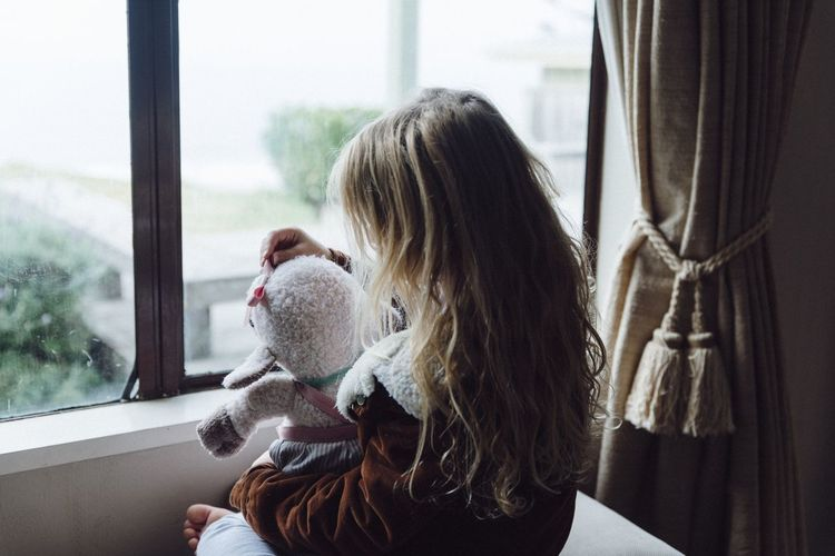 Girl playing with toy while sitting by window at home