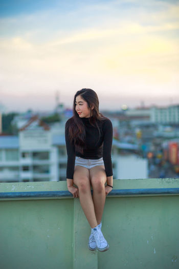 Young Woman Sitting On Railing Against Cityscape