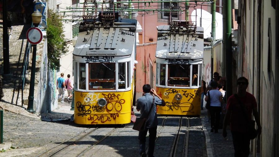 People and cable cars in city during sunny day