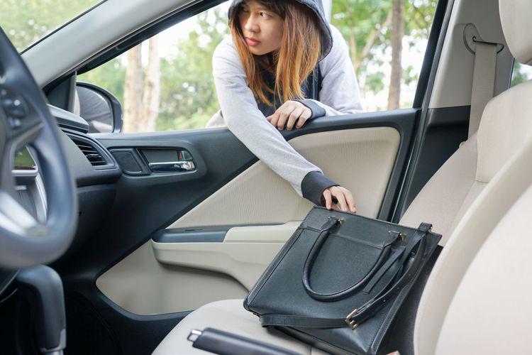 Burglar stealing purse from car