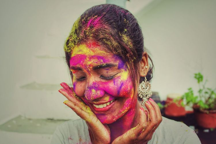 Smiling young woman with face paint during holi