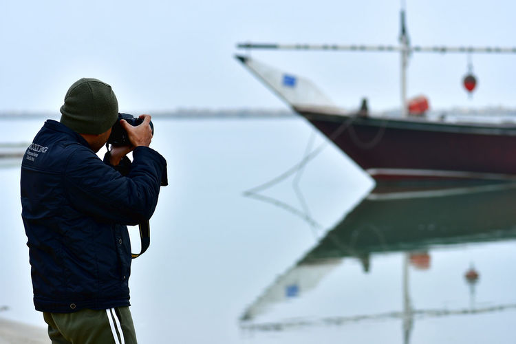 Photographer making photos on the seaside of boat on the water and the seaside view Man At Work Man With Hat Seashore Seaview Beach Taking Photos Taking Photos ❤ Boat On The Beach Boat On Water Boat Photography Camera - Photographic Equipment Day Man With Camera One Person Ourdoors Outdoors Photographing Real People Sea Sea And Sky Seascape Seaview Selective Focus Selfie Technology Water