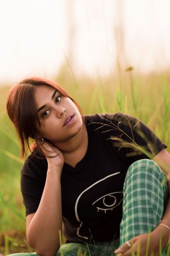 Portrait of beautiful young woman sitting on field