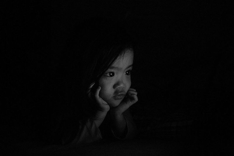 Close-Up Of Girl Sitting Against Black Background