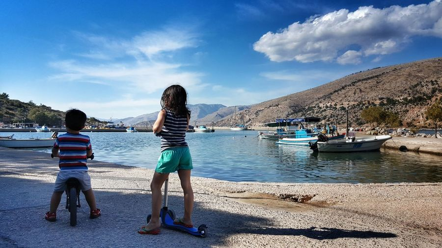 Rear View Of Girl With Push Scooter By Boy Against Lake