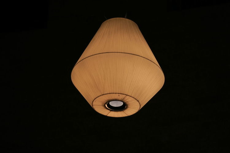 Low angle view of illuminated pendant light against black background