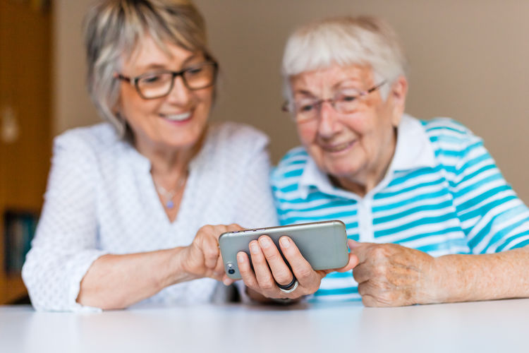 Smiling Senior Women Using Mobile Phone At Table In Home