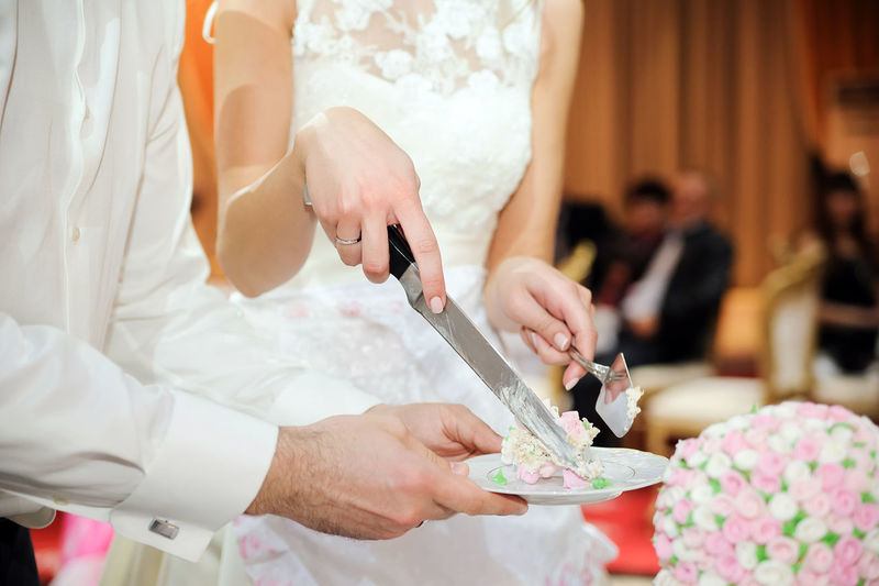 Midsection Of Bride Holding Knife With Cake On Plate By Waiter