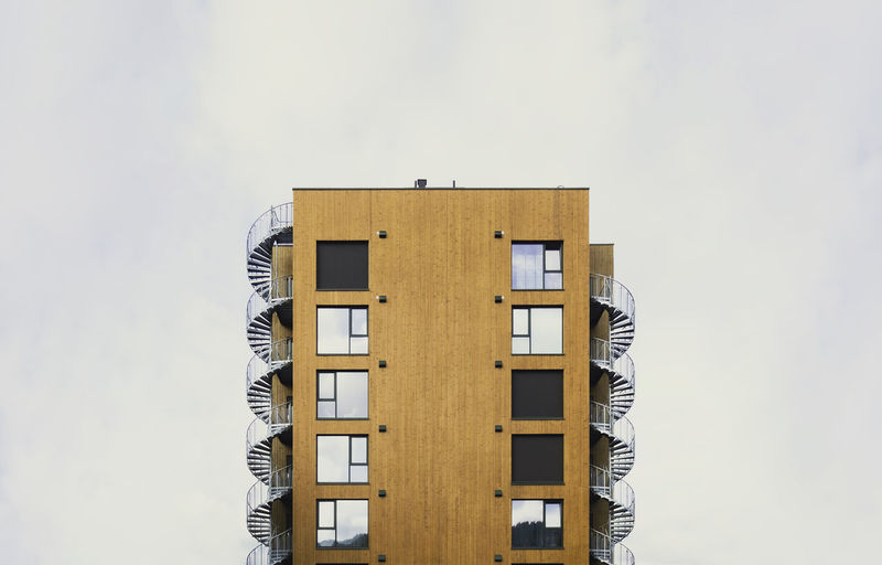 Modern residential building with wood cladding and spiral emergency stairs. lillehammer, norway.