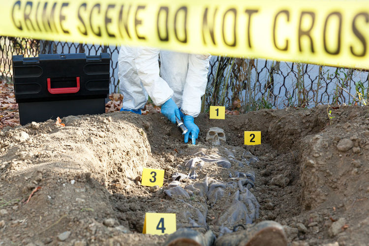 Forensic science specialist working at a crime scene. Exhumation site Cordon Tape Warning Warning Sign Evidence Marker Markers  Investigation Forensic Science Forensic Forensics Criminologist Criminology Crime Scene Crime Criminal Law Enforcement Protection Death Skull Body Part Mass Grave Grave Police At Work Dna Exhumation Examination