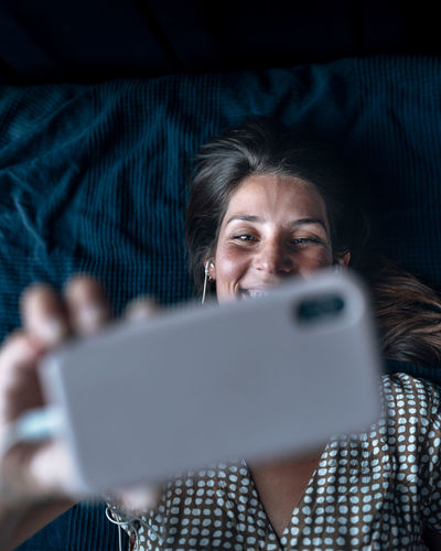 Directly above shot of woman on video call while lying in bed