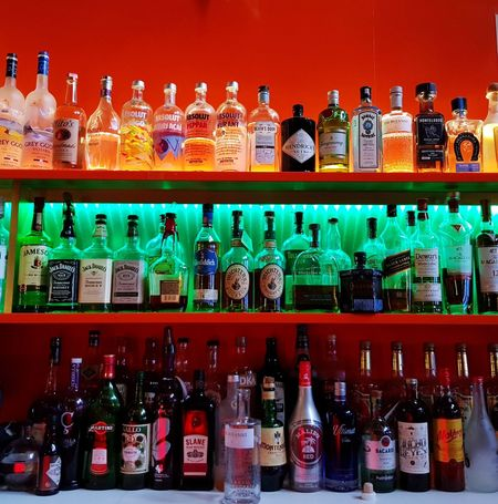 Alcohol bottles line up at the bar At The Bar Alcoholic Drink Alcohol Bottles Bar Drinks Bar Bottle Shelf In A Row Abundance Choice Food And Drink Alcohol Retail  Drink
