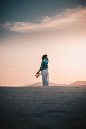 Standing in the desert Sunset Scenics - Nature Beauty In Nature Real People One Person Nature Land Standing Women Tranquil Scene Outdoors Desert Sand Dunas Fuerteventura Lifestyles Jeans Jeansjacket Jacket Girl Strawhat Sunlight Mountains Sky Environment Tranquility Cloud - Sky Travel Photography