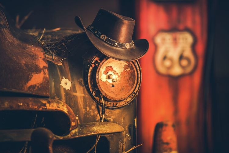 Route 66 Cowboys Concept. Cowboy Hat on the Rusty Classic Car with Broken Headlamp. Classic Car Cowboy Route 66 Wild West Abandoned Antique Art And Craft Close-up Damaged Focus On Foreground Hanging Illuminated Indoors  Lighting Equipment Metal Old Ornate Retro Styled Run-down Rusty Rusty Metal Selective Focus Still Life Vintage Western Script