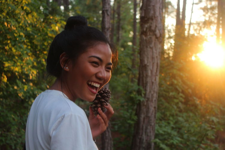 Portrait of smiling young woman in forest