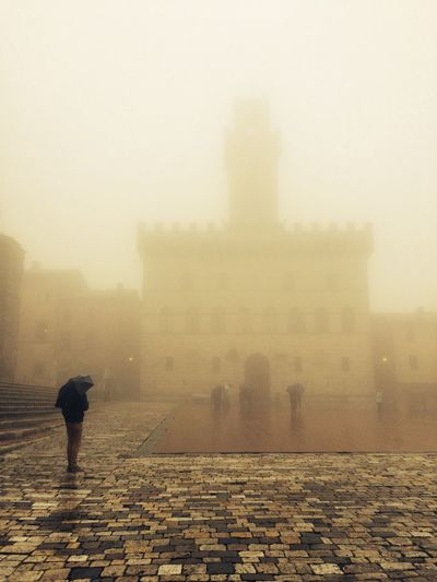 Man With Umbrella Standing By Cathedral During Foggy Weather