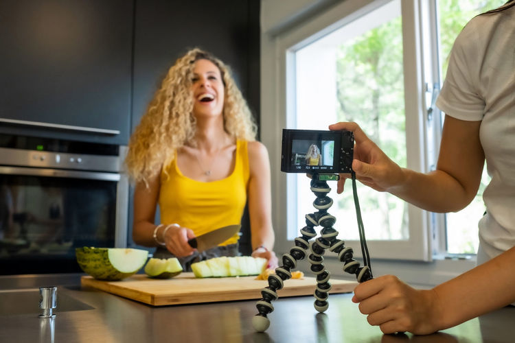 Midsection of woman filming friend cutting fruit