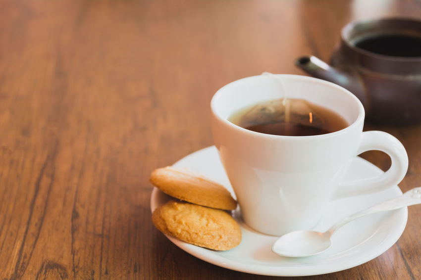 A tea cup with cookies on wooden table and copy space. Food And Drink Table Coffee Mug Drink Cup Coffee Cup Saucer Refreshment Coffee - Drink Food Crockery Freshness Indoors  Still Life Close-up Wood - Material Focus On Foreground Hot Drink Tea No People Tea Cup Non-alcoholic Beverage Sugar Cube Snack