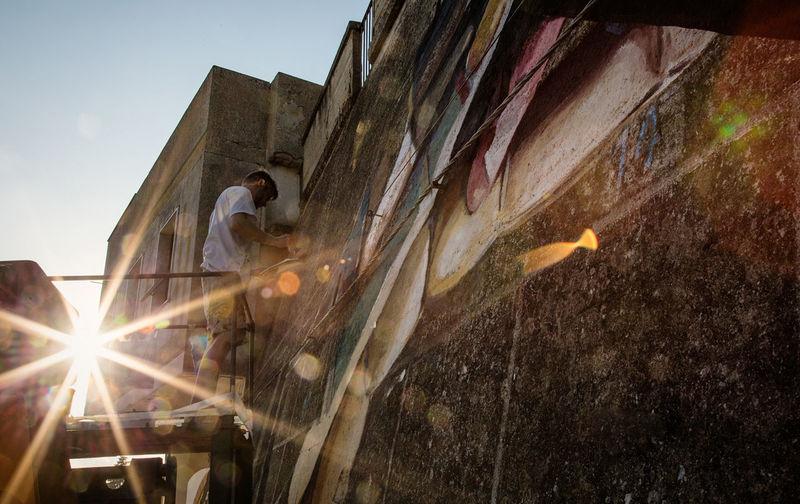 """e' una foto scattata durante un evento pieno di energia, un gruppo di ragazzi, molto artisti hanno deciso di abbellire la propria città con dei Murales, dipingendo su muri """"morti di cemento armato"""" trasformandoli in una vista di piacevoli colori. Beautiful City Cityscape Muralesart Outdoors People Sunshine The City Light First Eyeem Photo"""