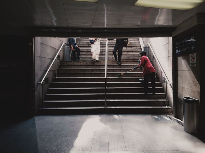 Low Section Of People Walking By Cleaner Cleaning Staircase At Subway Station