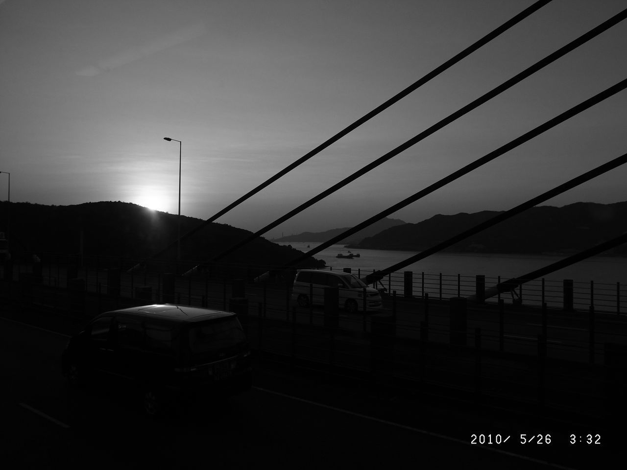 sky, transportation, mode of transportation, built structure, architecture, no people, nature, building exterior, cable, railing, land vehicle, car, sunset, street, outdoors, city, barrier, motor vehicle, sunlight, silhouette