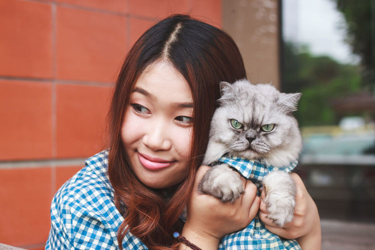 Close-up of thoughtful young woman holding cat against brick wall