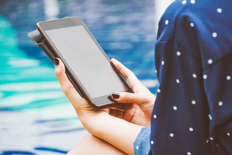 Cropped hands of woman using digital tablet while sitting at poolside
