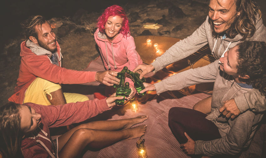 High angle view of friends toasting beer bottles while sitting on blanket at night