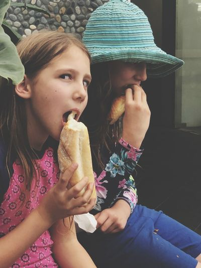 Portrait of girl eating food with sister while sitting outdoors