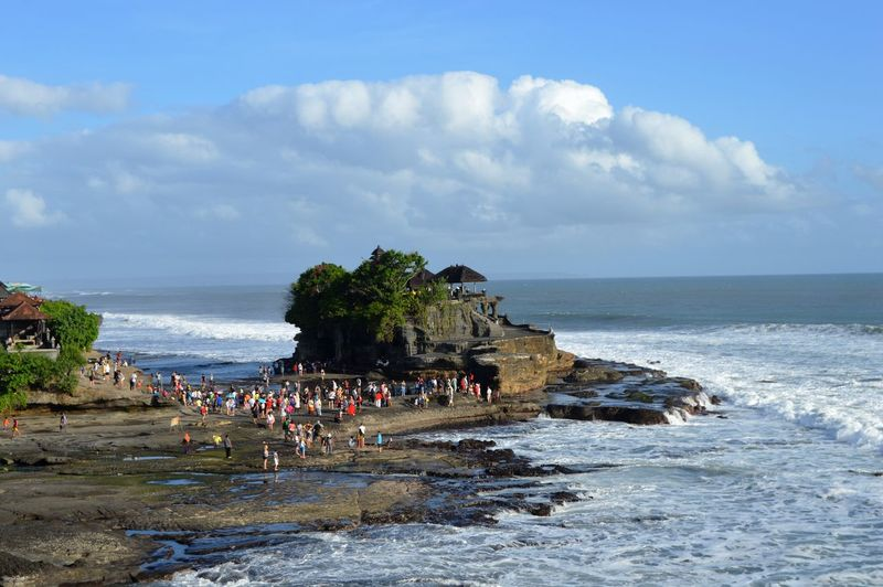 High angle view of crowd and tanah lot temple by sea