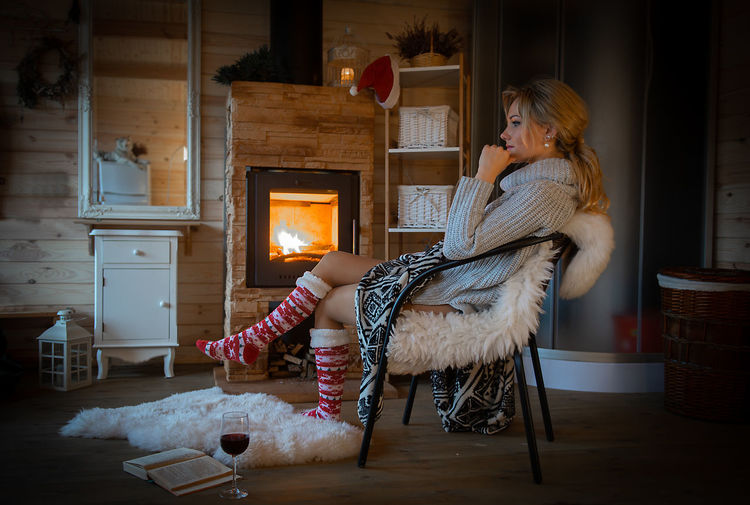 Toned photo of woman at fireplace during winter