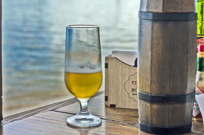 Drinking beer by the sea. Alcohol Alcoholic Drink Beer Beer - Alcohol Beer Glass Close-up Day Drink Drinking Glass Food And Drink Freshness Frothy Drink Liqueur Nature No People Outdoors Refreshment Sea Sky Table Water