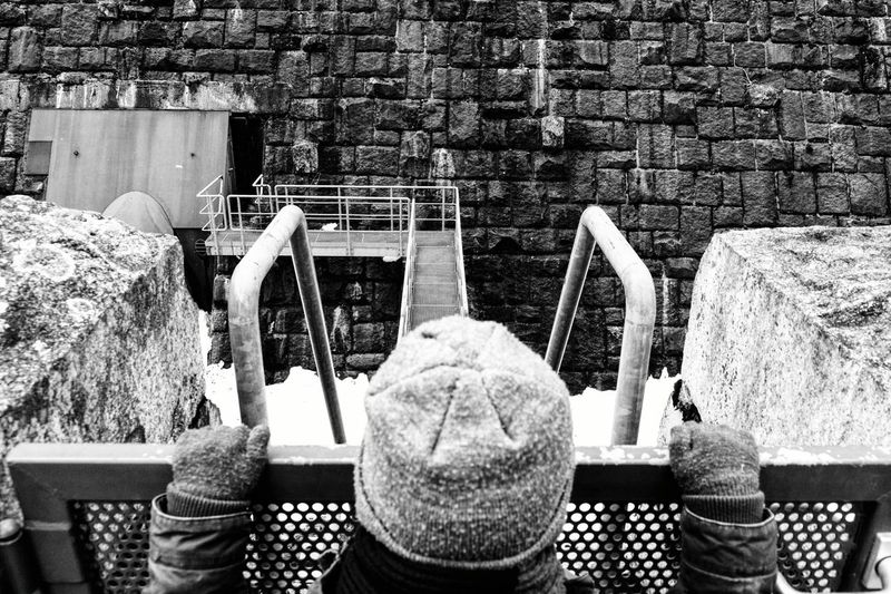 Rear View Of Boy Standing By Fence Against Brick Wall During Winter