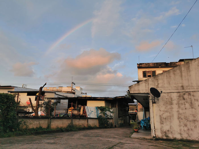 Rainbow over houses in town against sky
