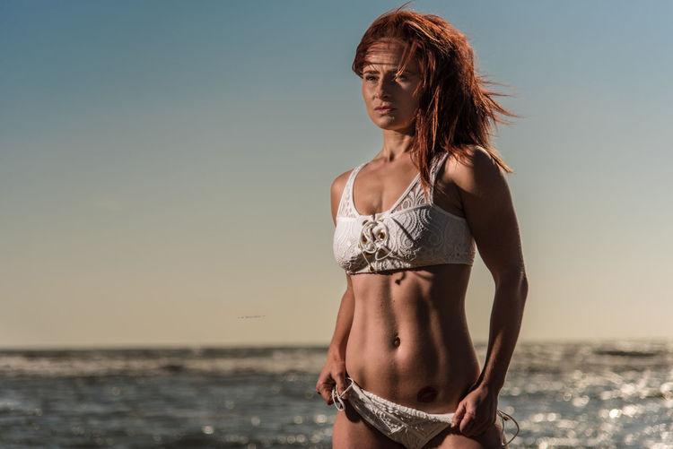 Sensuous Female Model Standing In Bikini At Beach Against Sky