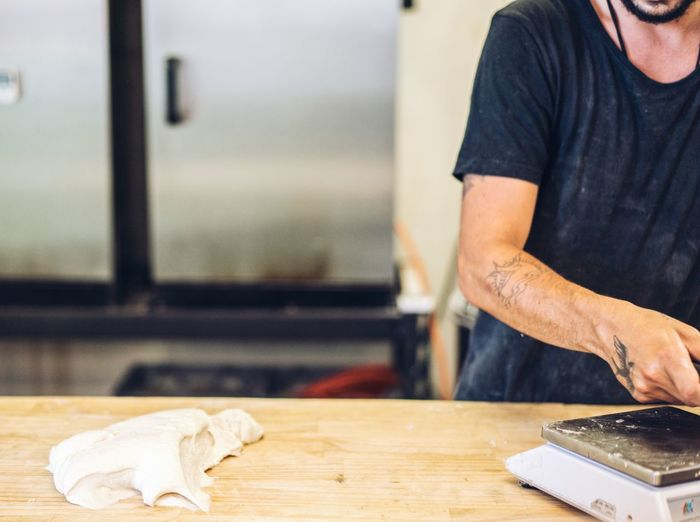 Man working on table making sourdough bread