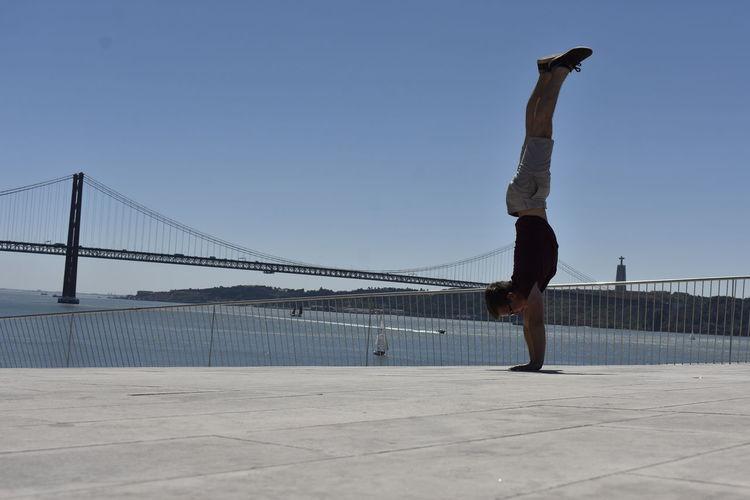 Man jumping on bridge against clear sky