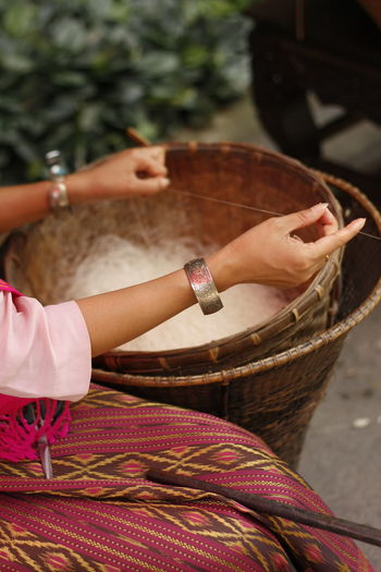 Midsection of woman holding basket thread
